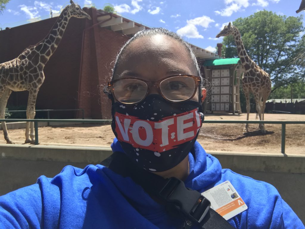 me in vote mask standing in front of kipele and heshimu