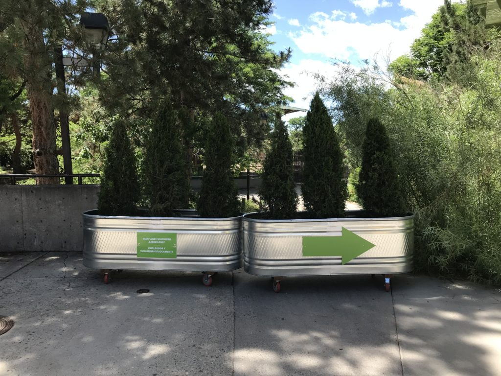 galvanized tubs making walking path barrier with a green arrow